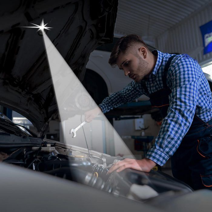 Auto mechanic working under raised car hood with Button Lamp attached