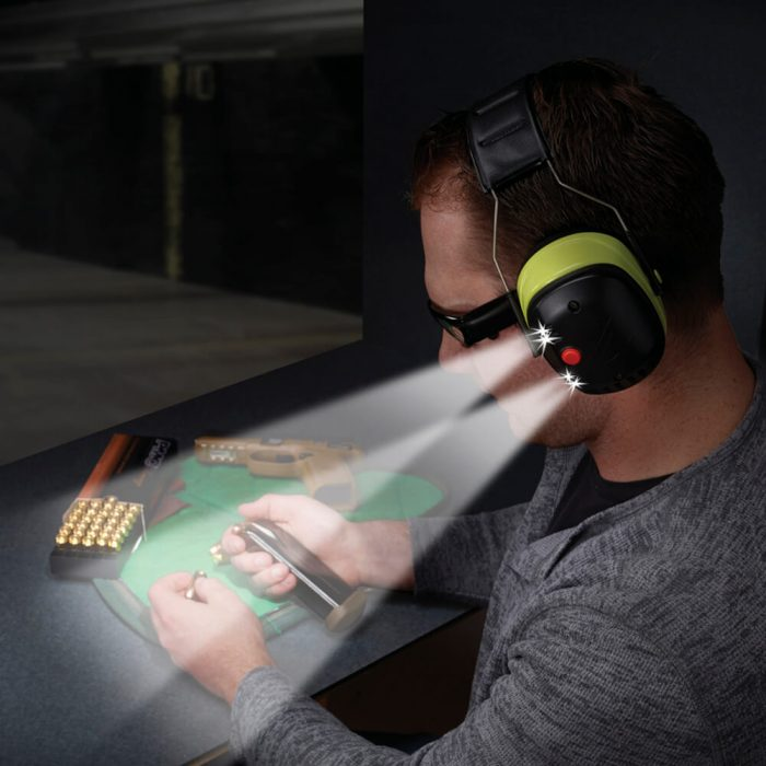 Man wearing LED Lighted Earmuffs at workbench in low lighting