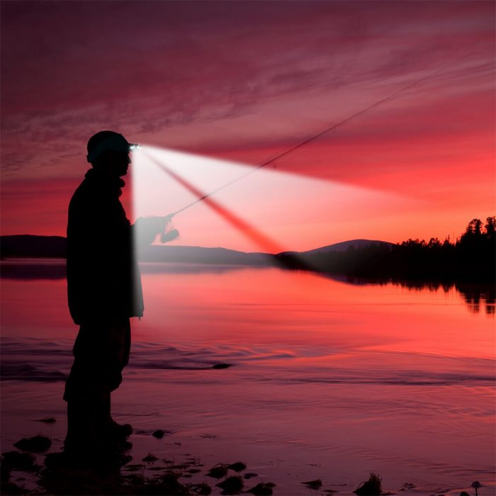 Fisherman wearing Powercap 25/10 microfiber LED lighted visor next to lake in low lighting