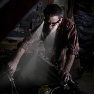 Car mechanic using LIGHTSPECS LED safety glasses under hood of car