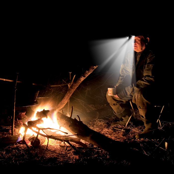 hunter wearing lighted beanie next to a camp fire