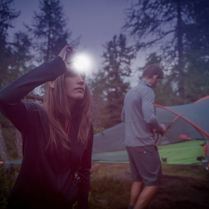 woman camping with headlamp