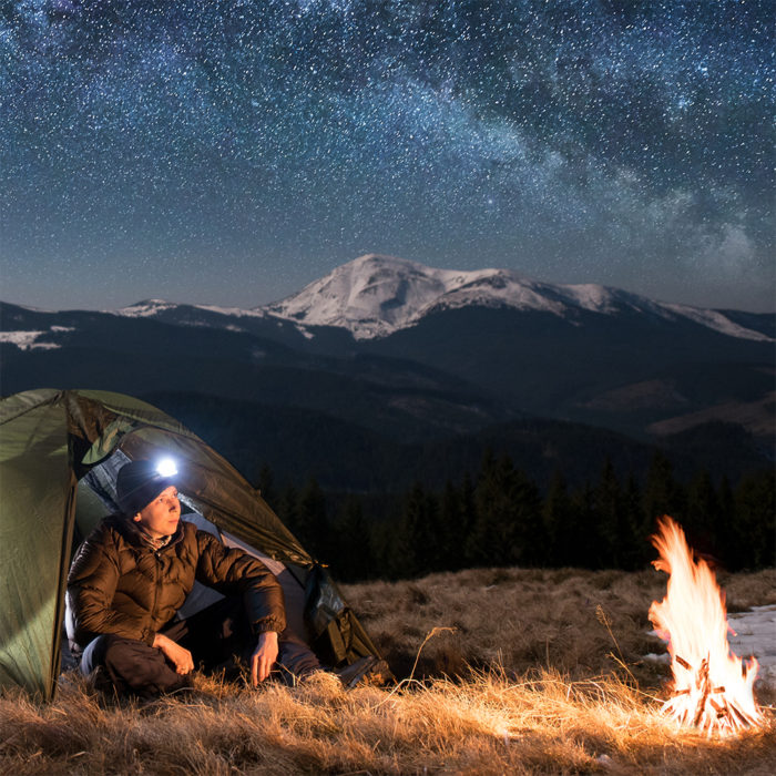man camping with lighted beanie