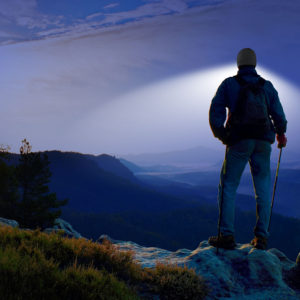 man hiking mountain with lighted beanie