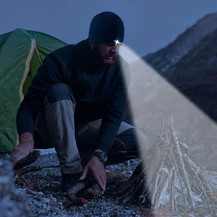 man at a campfire with a lighted beanie
