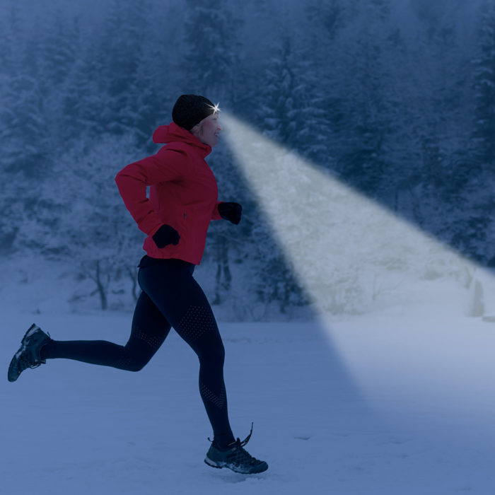 women running through snow with lighted beanie