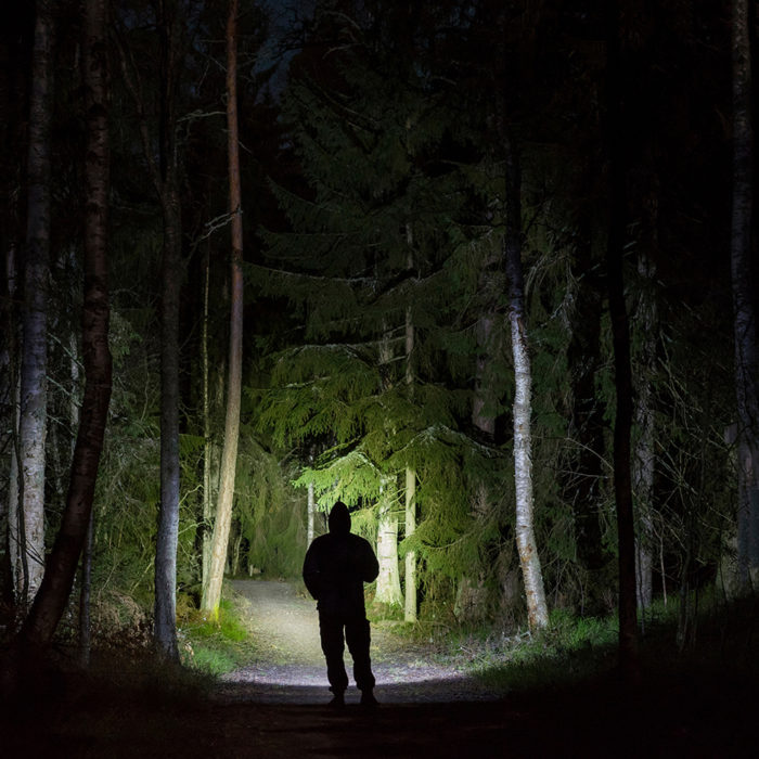 man walking in woods with flashlight