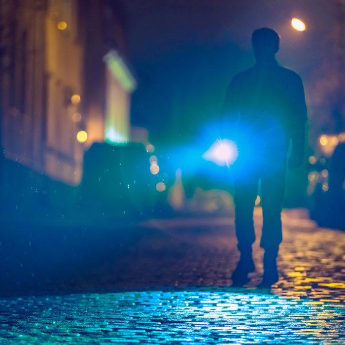 man walking street with flashlight